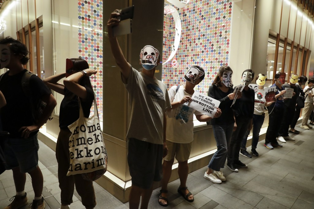 Protesters takes selfies while wearing masks during a protest in Hong Kong, Friday, Oct. 18, 2019. Hong Kong pro-democracy protesters are donning cart...
