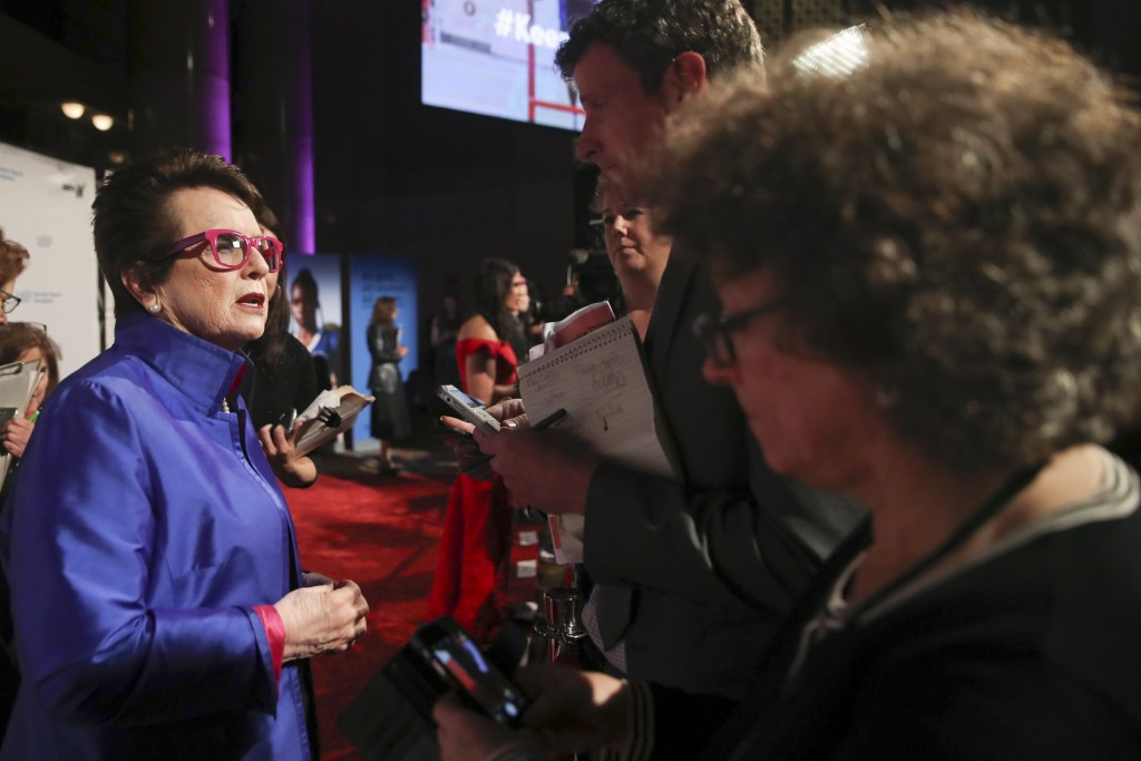 In this Wednesday, Oct. 16, 2019, photo tennis great and founder of Women's Sports Foundation Billie Jean King, left, talks to reporters on the red ca...