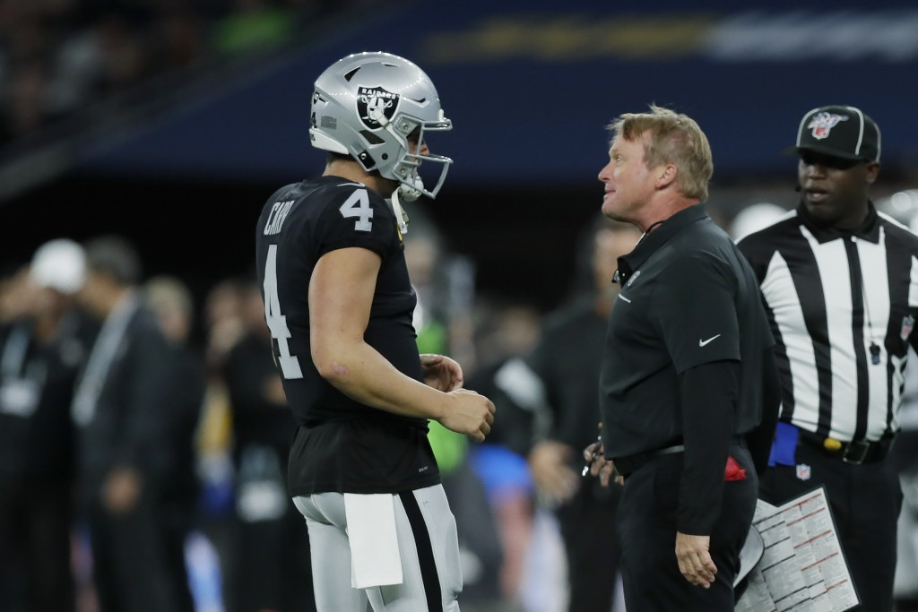 Oakland Raiders head coach Jon Gruden, front right, talks with quarterback Derek Carr (4) during the first half of an NFL football game against the Ch...