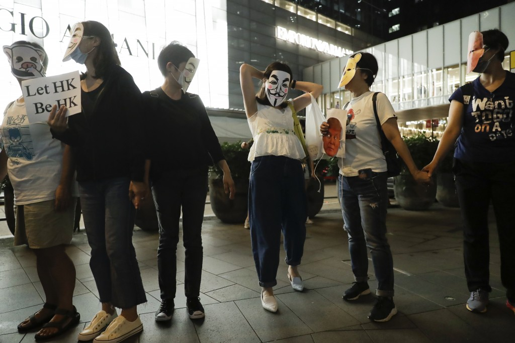 Protesters wear masks during a protest in Hong Kong, Friday, Oct. 18, 2019. Hong Kong pro-democracy protesters are donning cartoon/superhero masks as ...