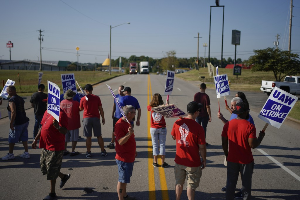 FILE - In this Sept. 16, 2019, file photo striking plant workers block the passage of two trucks outside the General Motor assembly plant in Bowling G...