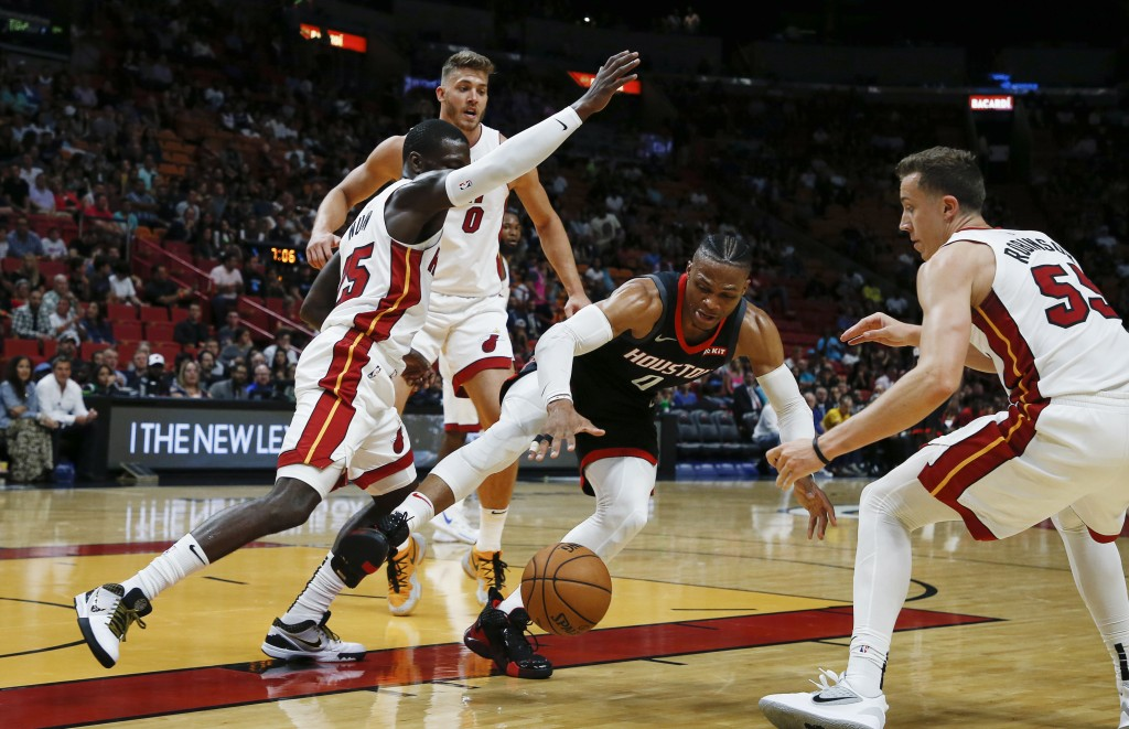 Houston Rockets guard Russell Westbrook (0) grabs a rebound between Miami Heat defenders, including Daryl Macon (15) and Duncan Robinson (55), during ...