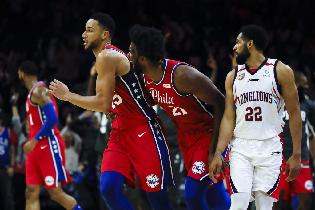 Philadelphia 76ers' Joel Embiid, center right, celebrates with Ben Simmons, center left, after he shot a 3-pointer to end the second quarter as Guangz...