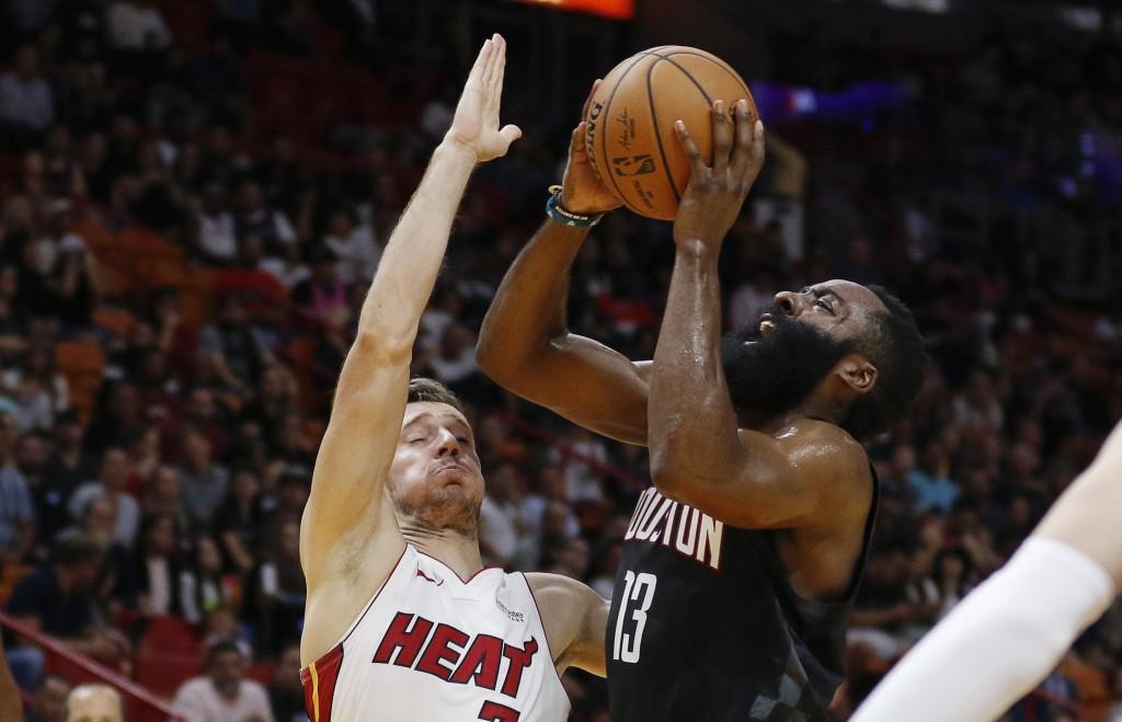 Houston Rockets guard James Harden (13) shoots next to Miami Heat guard Goran Dragic (7) during the first quarter of an NBA preseason basketball game ...