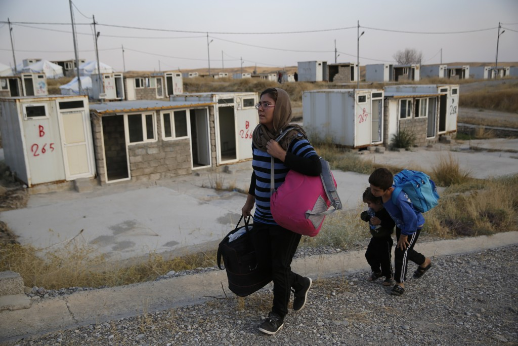 FILE - In this Oct. 17, 2019 file photo, Salwa Hanna with her children, who are newly displaced by the Turkish military operation in northeastern Syri...
