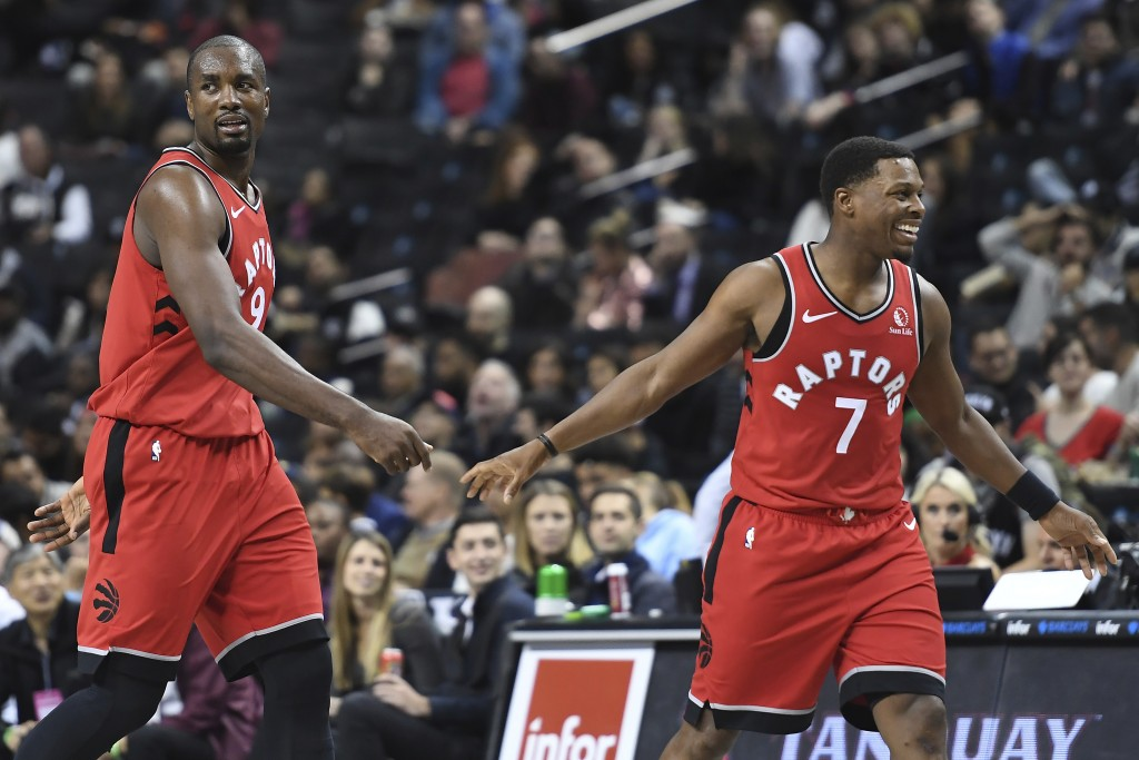 Toronto Raptors guard Kyle Lowry (7) and forward Serge Ibaka (9) react during the fourth quarter of a preseason NBA basketball game against the Brookl...