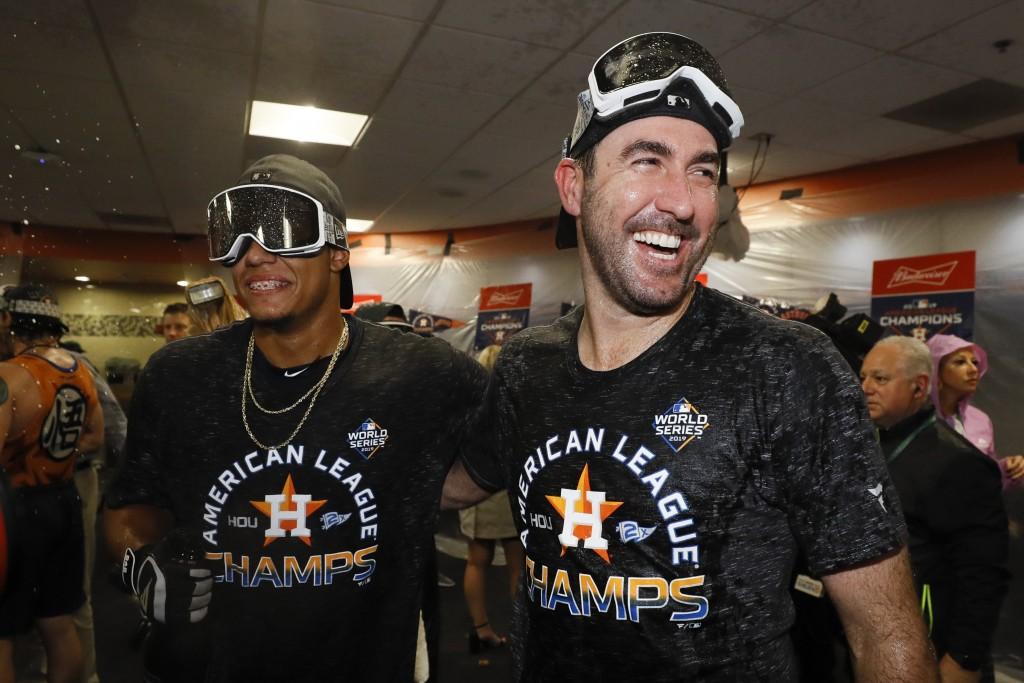 Houston Astros starting pitcher Bryan Abreu, left, and starting pitcher Justin Verlander celebrate in the locker room after winning Game 6 of baseball...