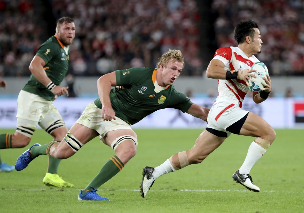 Japan's Kenki Fukuoka, right, is chased by South Africa's Pieter-Steph du Toit during the Rugby World Cup quarterfinal match at Tokyo Stadium in Tokyo...