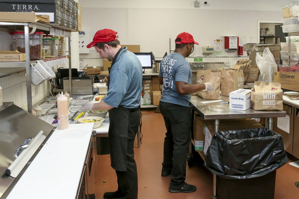 William Burns, left, general manager of the B.Good ghost kitchen inside Kitchen United's Chicago, Ill., location prepares food for delivery on Aug. 29...