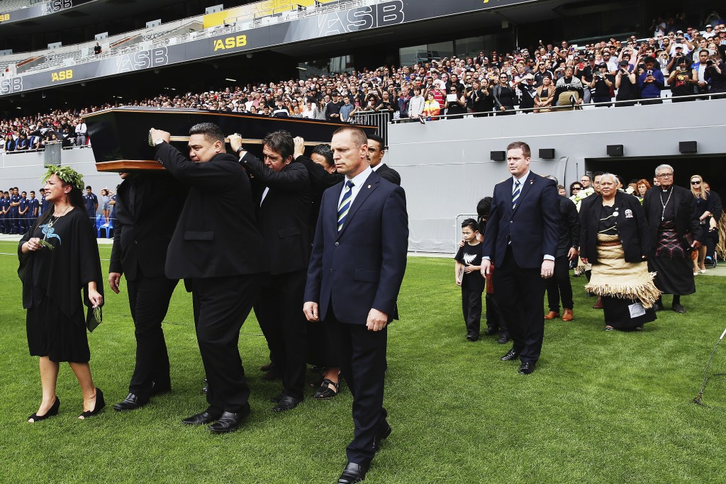 FILE - In this Nov. 30, 2015, file photo, the casket carrying the body of Jonah Lomu is carried onto the field during the public memorial for the form...