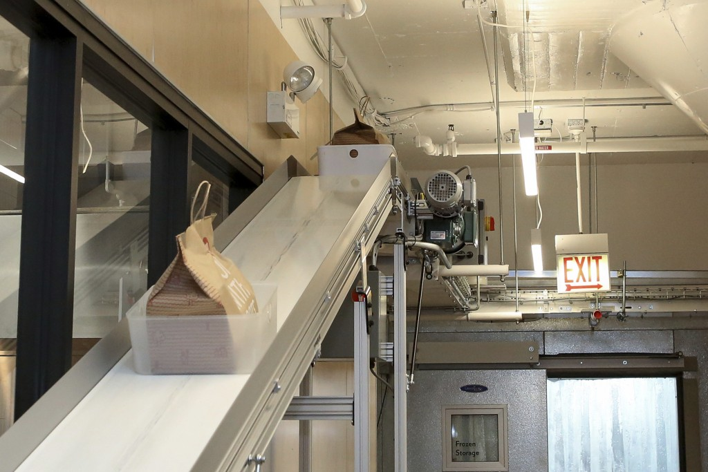 A conveyor belt takes bags of food from ghost restaurants to a room where delivery drivers pick up orders at Kitchen United's Chicago location on Aug....