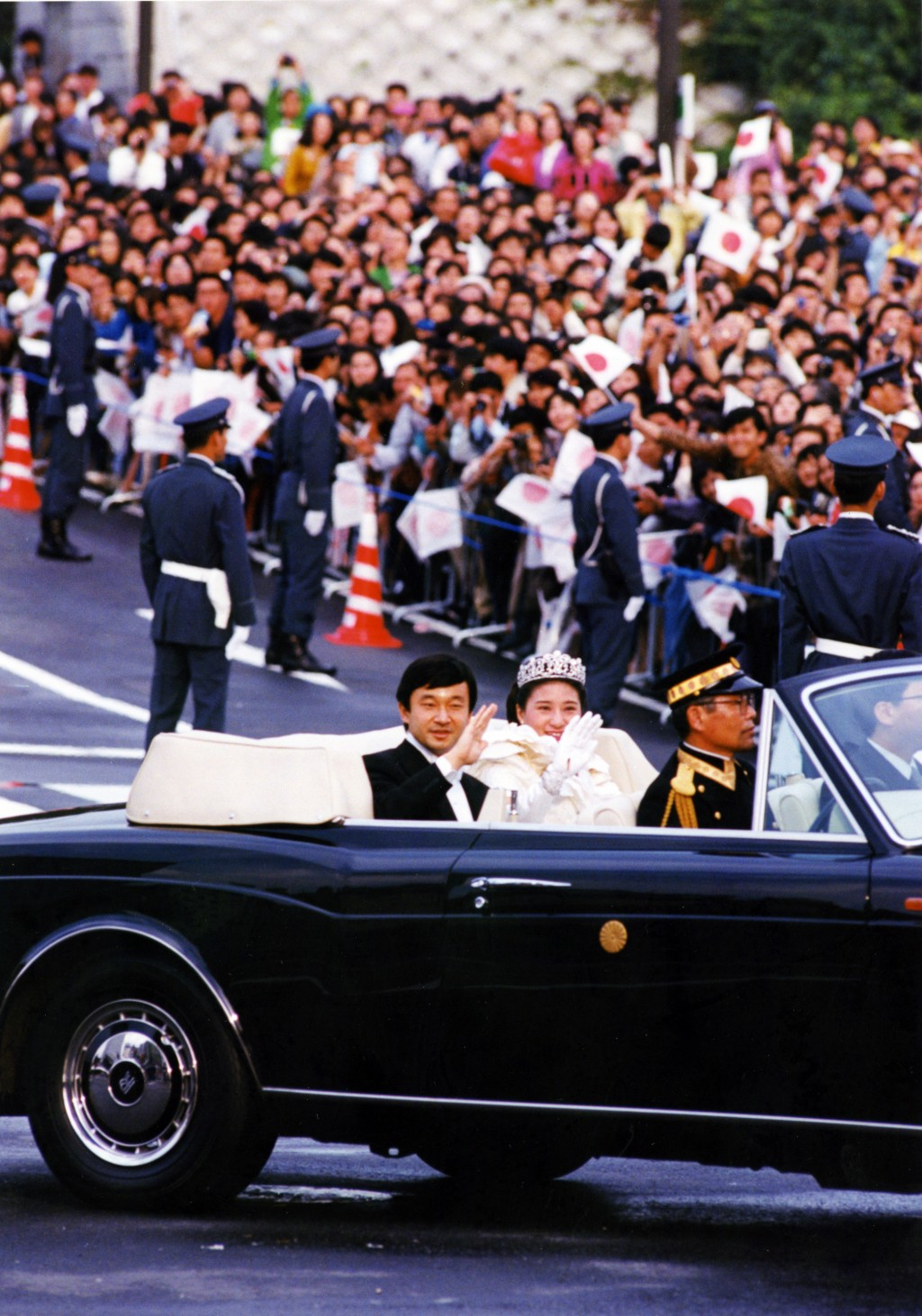 FILE - In this June 9, 1993, file photo, then Crown Prince Naruhito and Princess Masako wave to well-wishers from a limousine during a parade through ...