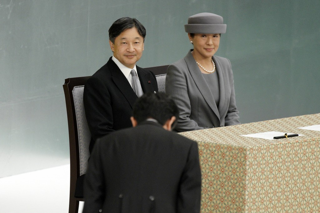 FILE - In this Aug. 15, 2019, file photo, Japanese Emperor Naruhito, and Empress Masako, look at Japanese Prime Minister Shinzo Abe bowing during a me...