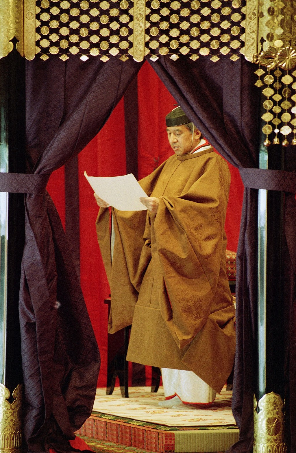 FILE - In this Nov. 12, 1990, file photo, then Japan's Emperor Akihito reads an address as he formally ascends to the Chrysanthemum Throne at the impe...