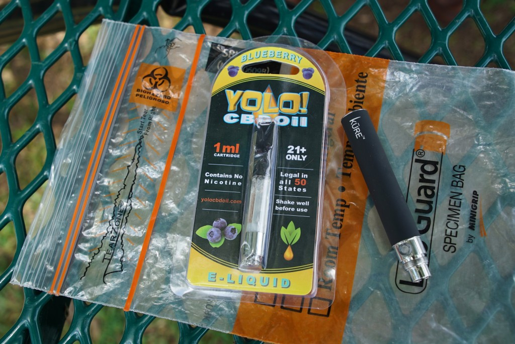 FILE - In this May 8, 2019, file photo, a Yolo! brand CBD oil vape cartridge sits alongside a vape pen on a biohazard bag on a table at a park in Nine...