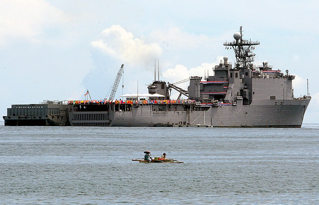 FILE - In this May 31, 2007, file photo, a Filipino fisherman sails past the USS Harpers Ferry, the U.S. Navy's amphibious warship, as it anchors off ...