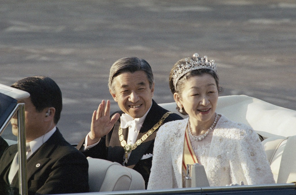 FILE - In this Nov. 12, 1990, file photo, then Japan's Emperor Akihito, center, waves as then Empress Michiko smiles as they start an open car parade ...