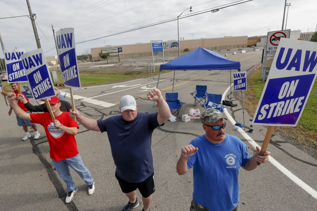 FILE - In this Sept. 16, 2019, file photo picketers carry signs at one of the gates outside the closed General Motors automobile assembly plant in Lor...