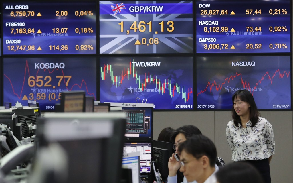 Currency traders watch monitors at the foreign exchange dealing room of the KEB Hana Bank headquarters in Seoul, South Korea, Tuesday, Oct. 22, 2019. ...