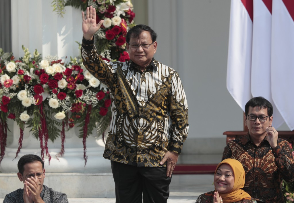 Newly appointed Defense Minister Prabowo Subianto who is the former rival of Indonesian President Joko Widodo in last April's election, waves as he is...