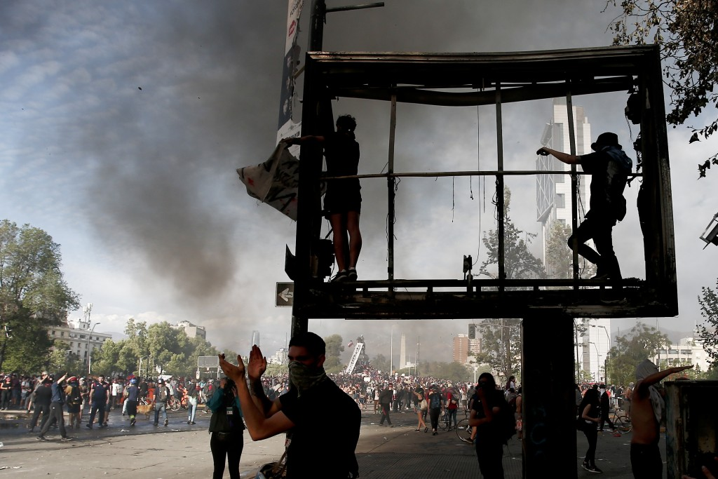 Anti-government demonstrators climb on a billboard in Santiago, Chile, Tuesday, Oct. 22, 2019. Unrest began last week when a rise in subway fares led ...
