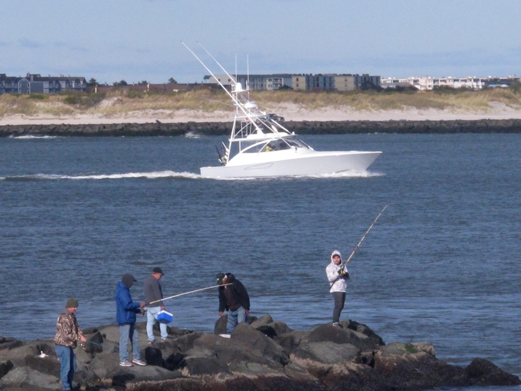 This Oct. 18, 2019 photo shows anglers fishing from a jetty as a large boat sails by in Atlantic City, N.J. On Oct. 22, 2019, a conference at Monmouth...