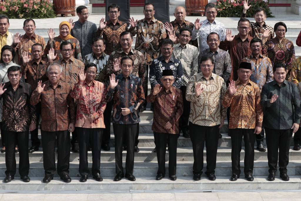 Indonesian President Joko Widodo, front row fourth from left, and his deputy Ma'ruf Amin, fifth from left, wave at the media as they pose for photogra...