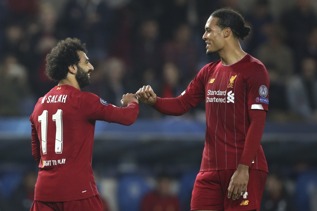 Liverpool's Mohamed Salah, left, is congratulated by Liverpool's Virgil van Dijk after scoring his sides fourth goal during a Champions League group E...