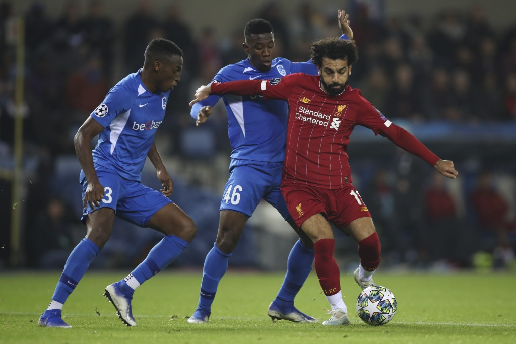 Liverpool's Mohamed Salah, right, vies for the ball with Genk's Jhon Lucumi, left, and Carlos Cuesta during a Champions League group E soccer match be...