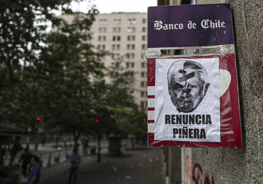 Placed by anti-government protesters, a poster featuring half the face of Chile's President Sebastian Piñera, left, and late dictator Augusto Pinochet...