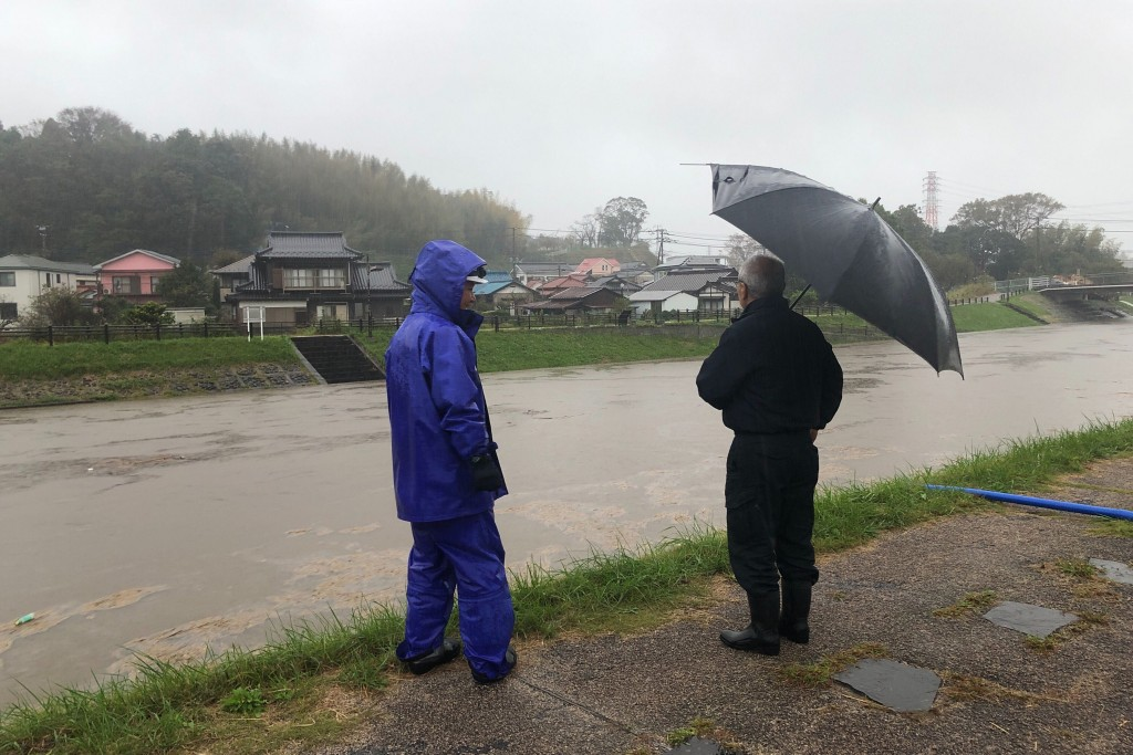 Men look at a swollen river due to heavy rain Friday, Oct. 25, 2019, in Narita, east of Tokyo. Torrential rain dumped from a low-pressure system hover...