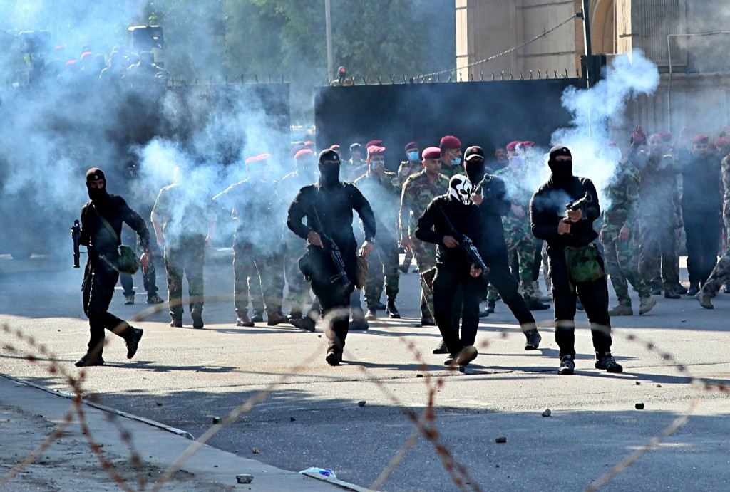 Iraqi security forces fire tear gas to disperse anti-government protesters during a demonstration in central Baghdad, Iraq, Friday, Oct. 25, 2019. Ira...