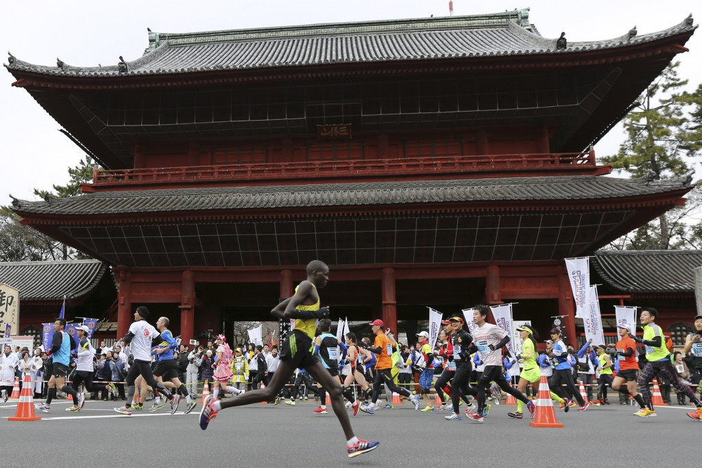 FILE - In this Feb. 23, 2014, file photo, runners pass by Zojoji Buddhist temple during the Tokyo Marathon in Tokyo. Tokyo Metropolitan Government was...