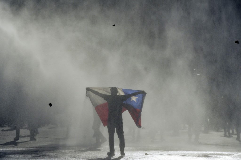 An anti-government protester holds out Chilean flag during clashes with police in Valparaiso, Chile, Friday, Oct. 25, 2019. A new round of clashes bro...