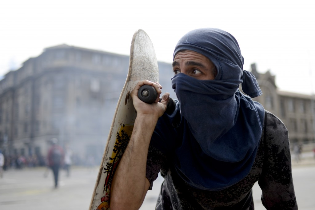 An anti-government protester peers out from behind his skateboard during clashes with police in Valparaiso, Chile, Friday, Oct. 25, 2019. A new round ...