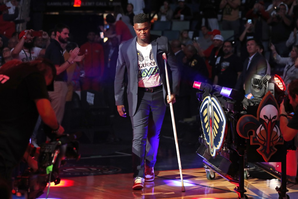 New Orleans Pelicans forward Zion Williamson walk onto the court with a crutch as he is introduced before an NBA basketball home-opener game against t...