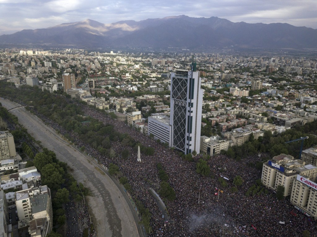 People gather for an anti-government protest in Santiago, Chile, Friday, Oct. 25, 2019. At least 19 people have died in the turmoil that has swept the...
