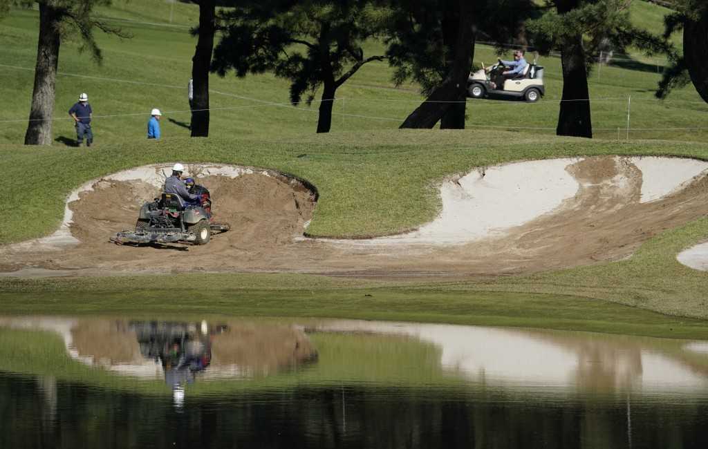 Grounds crew workers repair a bunker on the 10th hole before the start of the second round of the Zozo Championship PGA Tour at the Accordia Golf Nara...