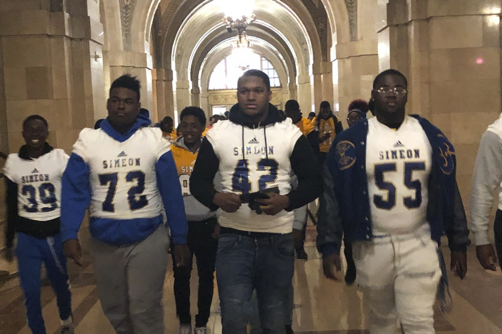 George Robinson (72) and Ronald Haggins (42) with members of the Simeon High School football team appear at City Hall Friday, Oct. 25, 2019, shows in ...