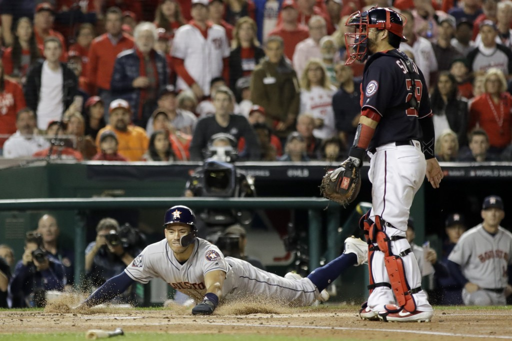 Houston Astros' Carlos Correa scores past Washington Nationals catcher Kurt Suzuki on a single by Josh Reddick during the second inning of Game 3 of t...