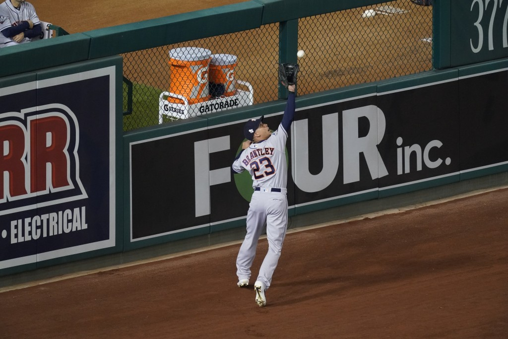 Houston Astros' Michael Brantley catches a ball hit by Washington Nationals' Trea Turner during the first inning of Game 3 of the baseball World Serie...