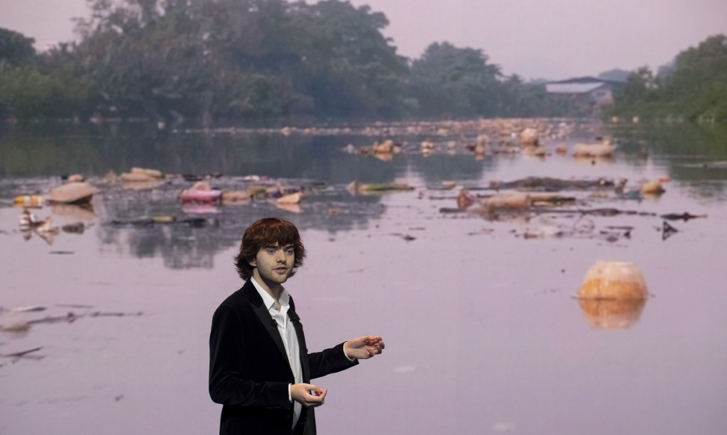 Young Dutch inventor Boyan Slat presents his plans for the Interceptor, a plastic-gathering floating device, in front of a video of a polluted river, ...