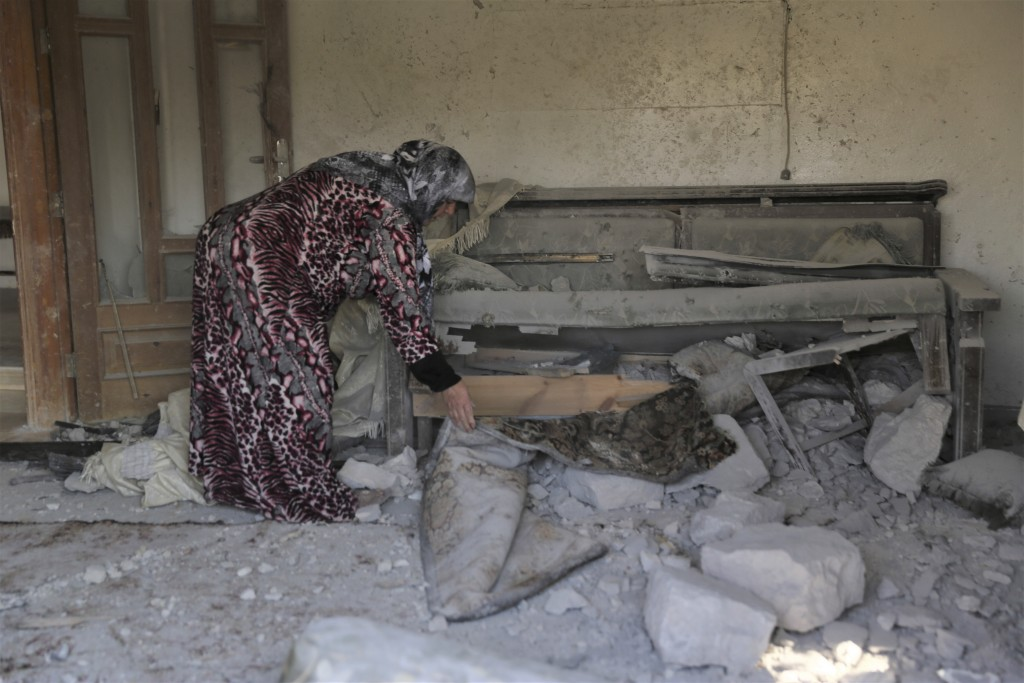 A woman checks damage to her home in the village of Barisha, in Idlib province, Syria, Sunday, Oct. 27, 2019, after an operation by the U.S. military ...