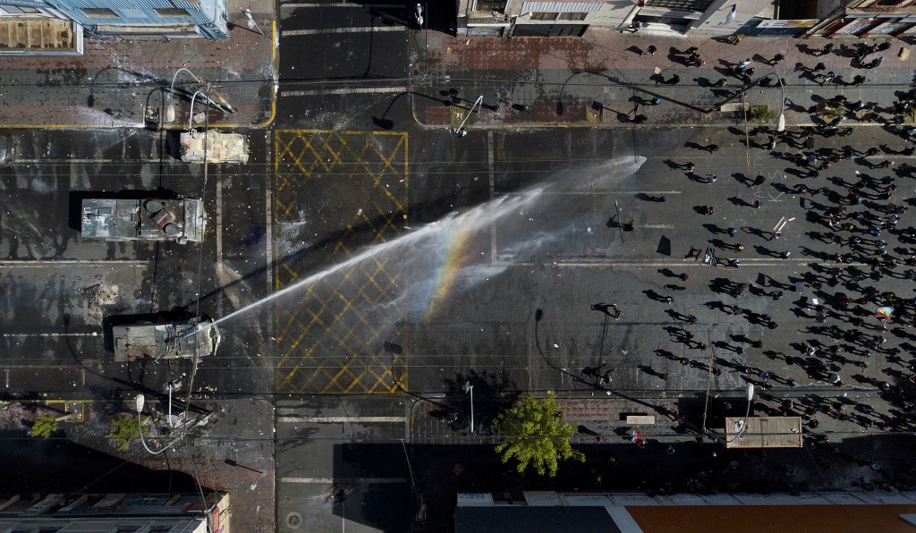 A police water cannon sprays anti-government demonstrators in Valparaiso, Chile, Saturday, Oct. 26, 2019. Clashes broke out Saturday as demonstrators ...