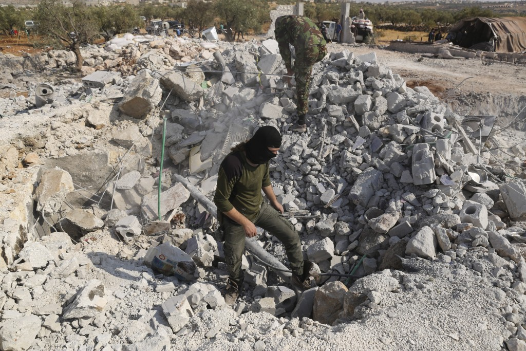 People look at a destroyed houses near the village of Barisha, in Idlib province, Syria, Sunday, Oct. 27, 2019, after an operation by the U.S. militar...