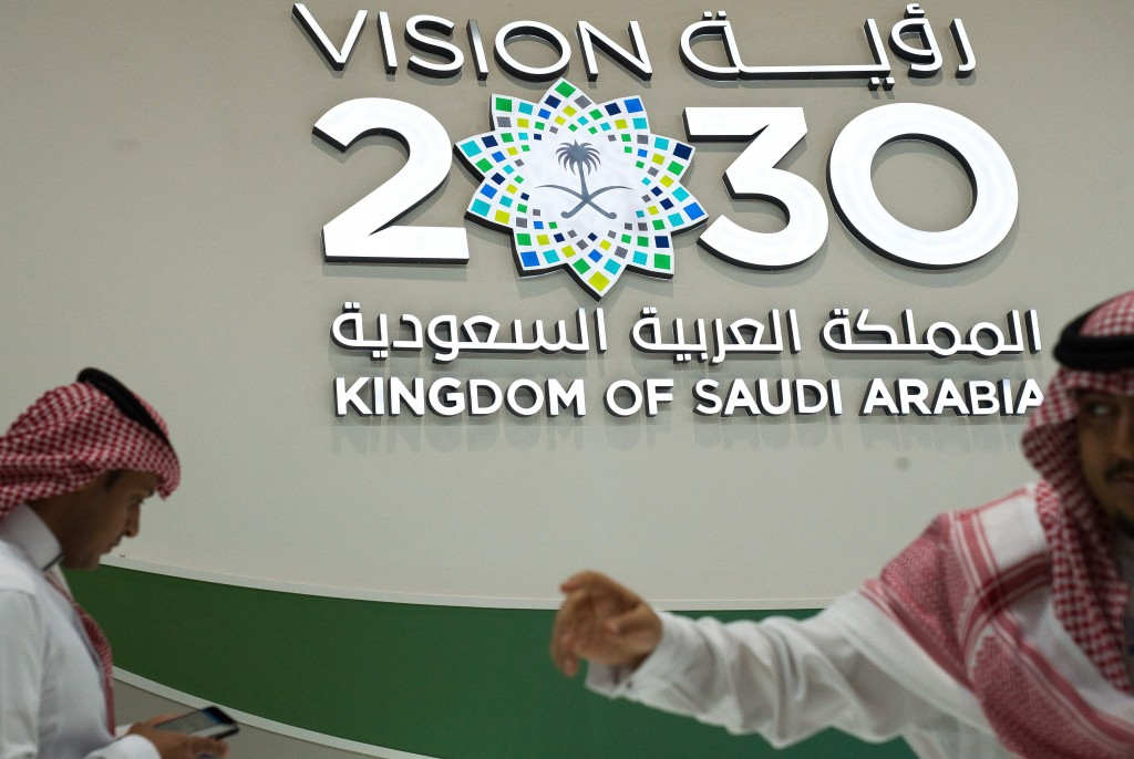 """FILE - In this Sept. 10, 2019, file photo, men walk past a """"Vision 2030"""" display at a stand about Saudi Arabia during the World Energy Congress in Abu..."""