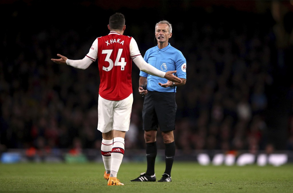 Arsenal's Granit Xhaka speaks to referee Martin Atkinson during the English Premier League soccer match at the Emirates Stadium, London, Sunday Oct. 2...