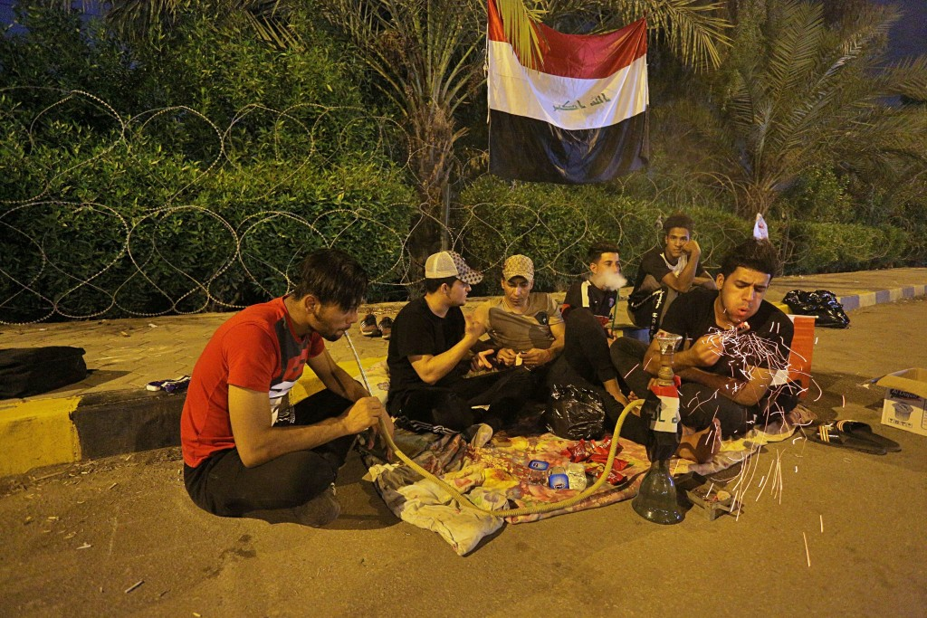Anti-government protesters rest and smoke a waterpipe during a sit-in near the closed Najaf provincial council, Iraq early Monday, Oct. 28, 2019. Prot...