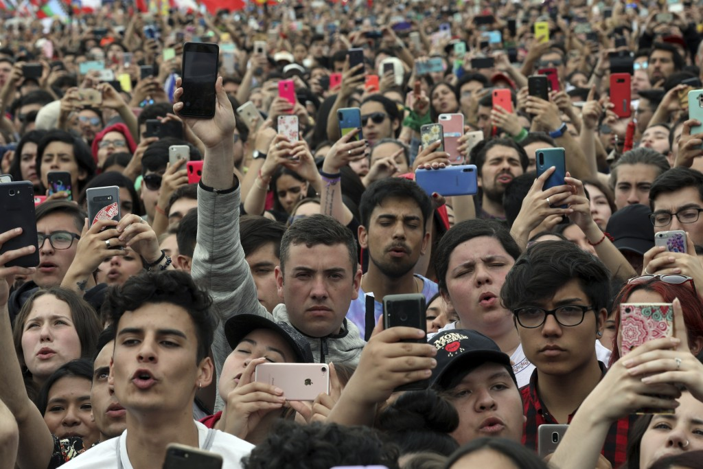 People takes photos and video with their cell phones during an anti-government music concert in O'Higgins Park in Santiago, Chile, Sunday, Oct. 27, 20...