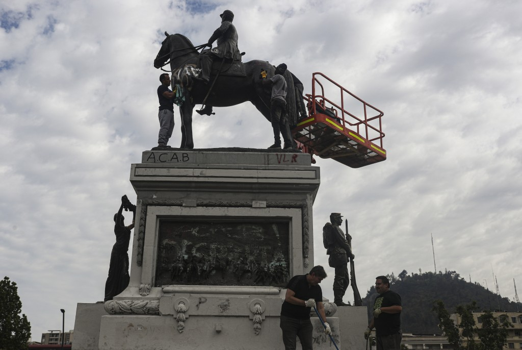 People clean the Gen. Manuel Baquedano monument in Plaza Italia, after it was vandalized amid days of demonstrations calling for better pay, pensions,...